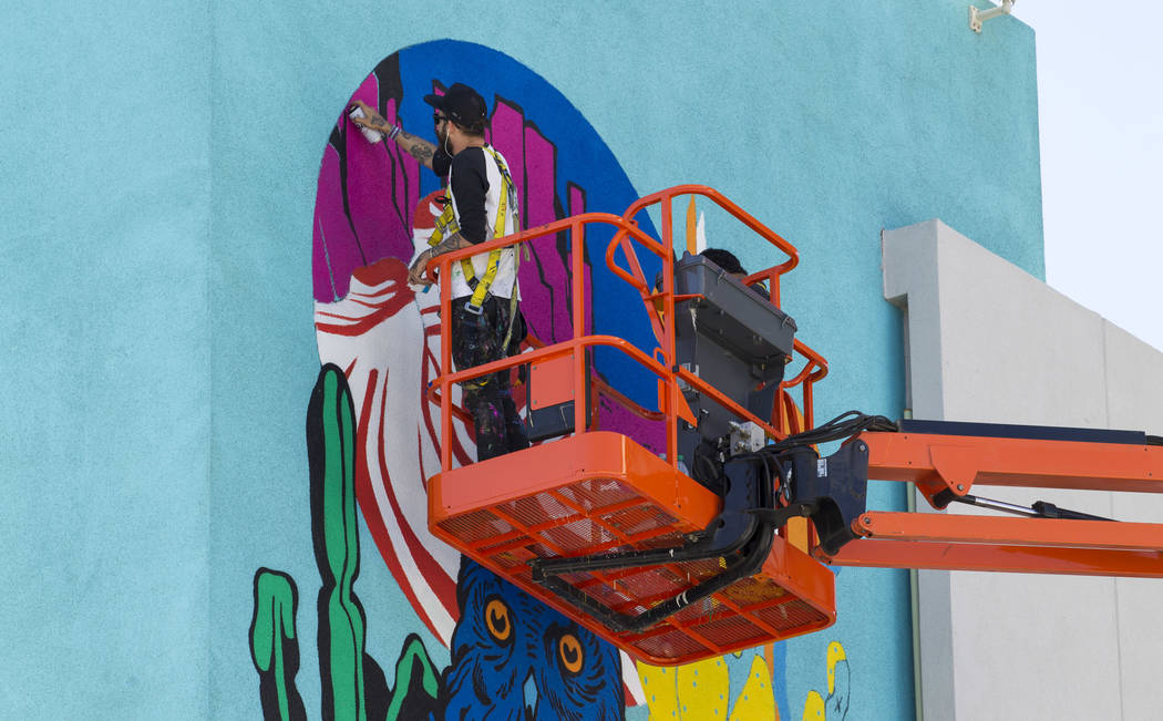 Painters work on a mural on the west side of the El Cortez building as preparations continue on the festival grounds of Life is Beautiful in downtown Las Vegas Thursday, Sept. 21, 2017. Richard Br ...