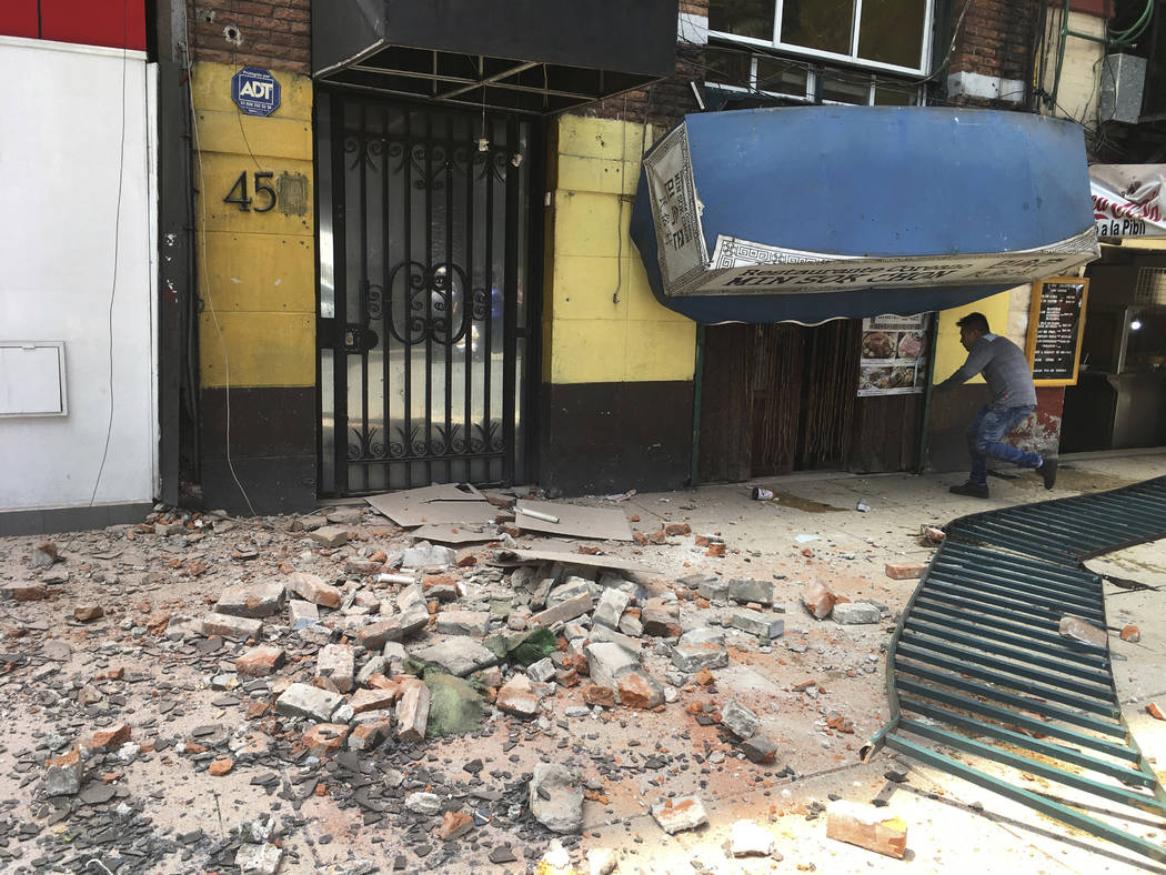 A man enters a damaged building after an earthquake in Mexico City, Tuesday, Sept. 19, 2017. A powerful earthquake jolted central Mexico on Tuesday, cracking building facades and scattering rubble ...