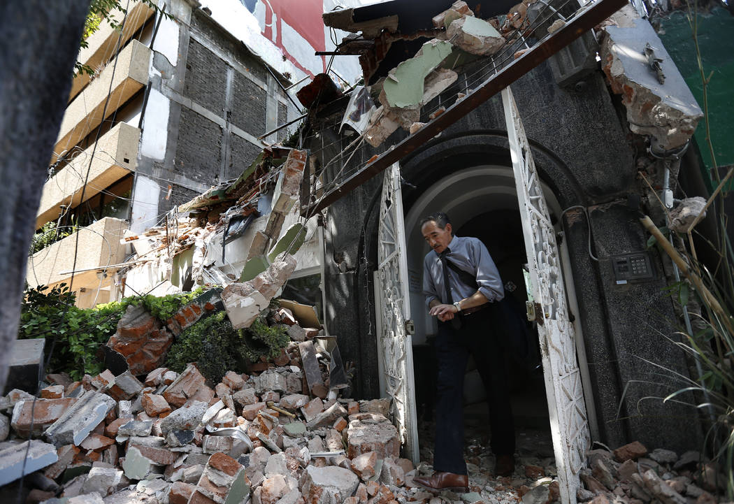 A man walks out of the door frame of a building that collapsed after an earthquake, in the Condesa neighborhood of Mexico City, Tuesday, Sept. 19, 2017. Throughout Mexico City, rescuer workers and ...