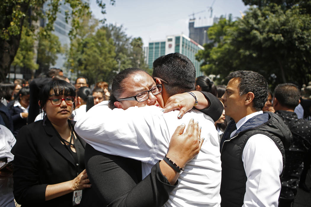 A woman is comforted after an earthquake in Mexico City Tuesday Sept. 19, 2017. A powerful earthquake jolted central Mexico on Tuesday, causing buildings to sway sickeningly in the capital on the  ...
