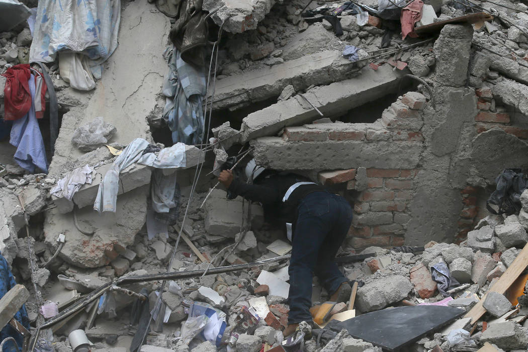 A construction worker searches a building that collapsed after an earthquake, in the Roma neighborhood of Mexico City, Tuesday, Sept. 19, 2017. A magnitude 7.1 earthquake has rocked central Mexico ...