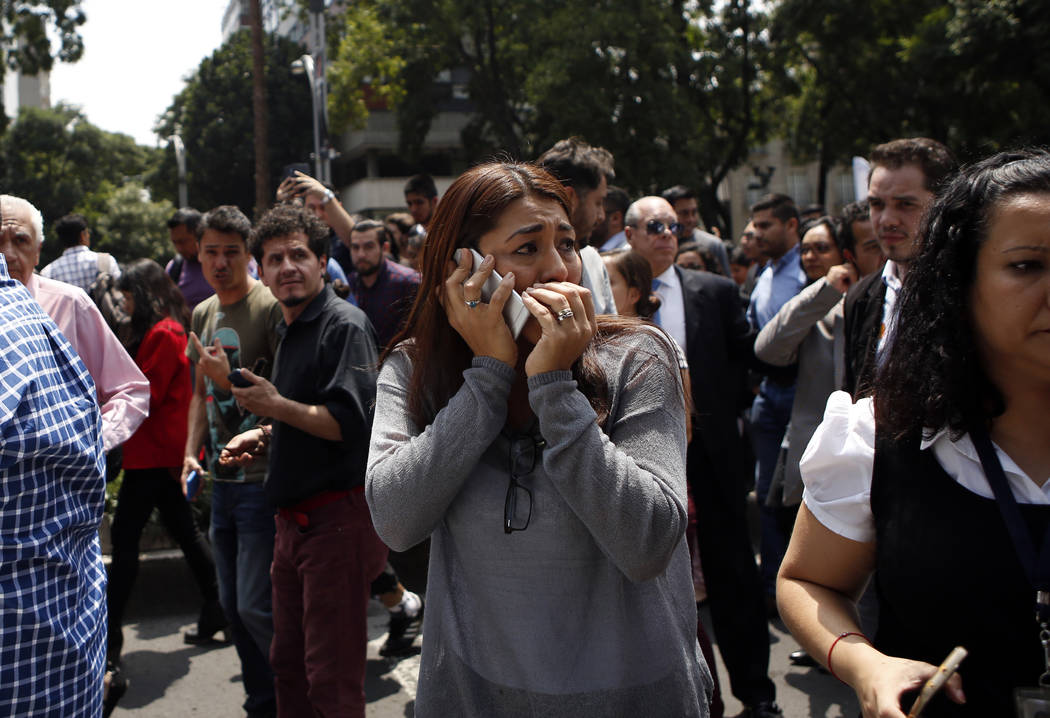 A woman speaks on her cell phone as people evacuated from office building gather in Reforma Avenue after an earthquake in Mexico City, Tuesday Sept. 19, 2017. A powerful earthquake jolted central  ...