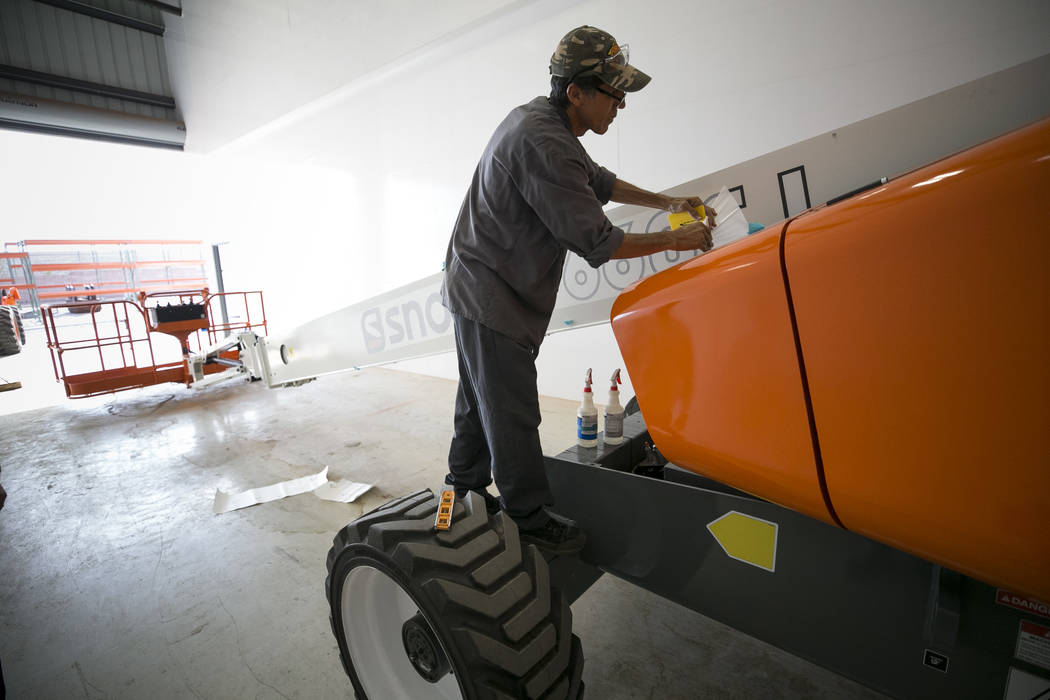 Assembly technician Walter Grijalva adds a decal to a Snorkel 660SJ boom lift of the assembly line of Xtreme Manufacturing, 8350 Eastgate Rd., in Henderson, Tuesday, Sept. 19, 2017. Richard Brian  ...