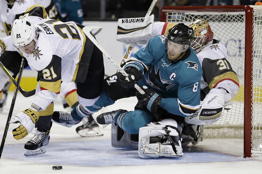 San Jose Sharks' Joe Pavelski (8) collides with Vegas Golden Knights goalie Calvin Pickard (31) as Golden Knights' Cody Eakin (21) defends during the third period of a preseason NHL hockey game, T ...