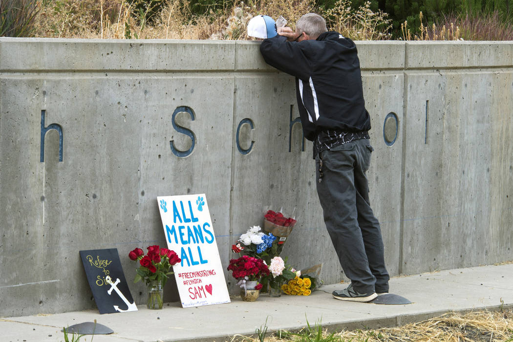 Freeman High School assistant football coach Tim Smetana grieves Sept. 14, 2017, after placing roses at a memorial to the shooting victims at the school in Rockford, Washington. Students returned  ...