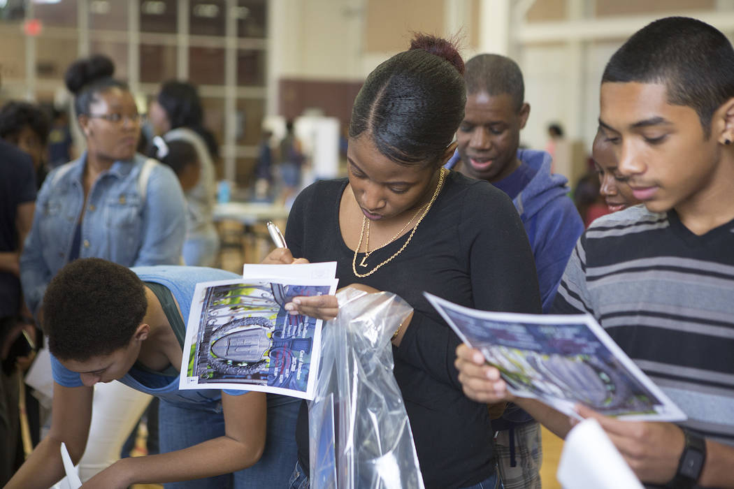Legacy junior Loniesha F., who didn't want to publish her last name, fills out paperwork at Howard University's booth during the 18th annual Historically Black Colleges & Universities Recruitm ...