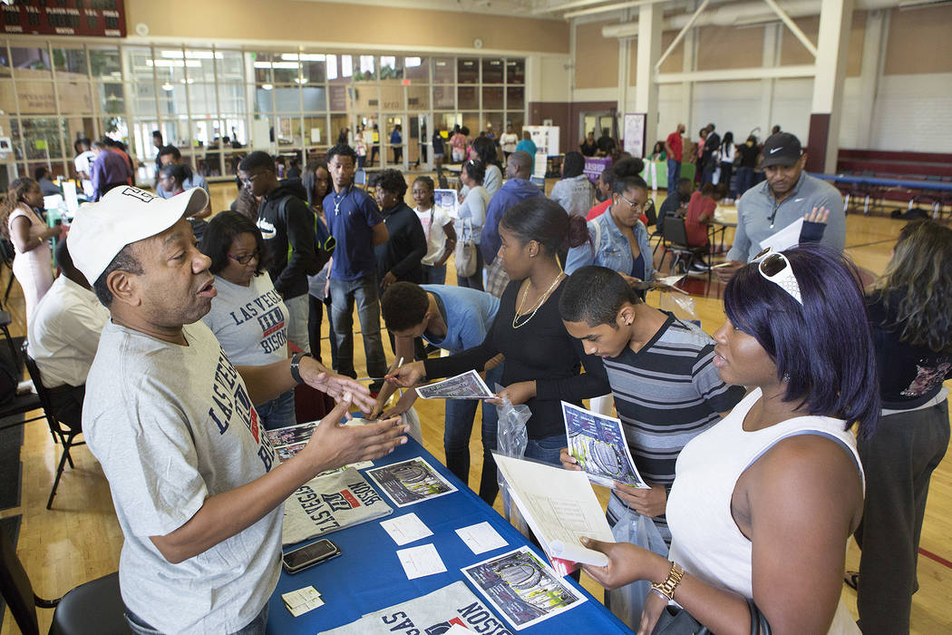 Howard University alumnus Ryan Myers, left, answers questions about the university  from a crowd of people during the 18th annual Historically Black Colleges & Universities Recruitment Fair at ...