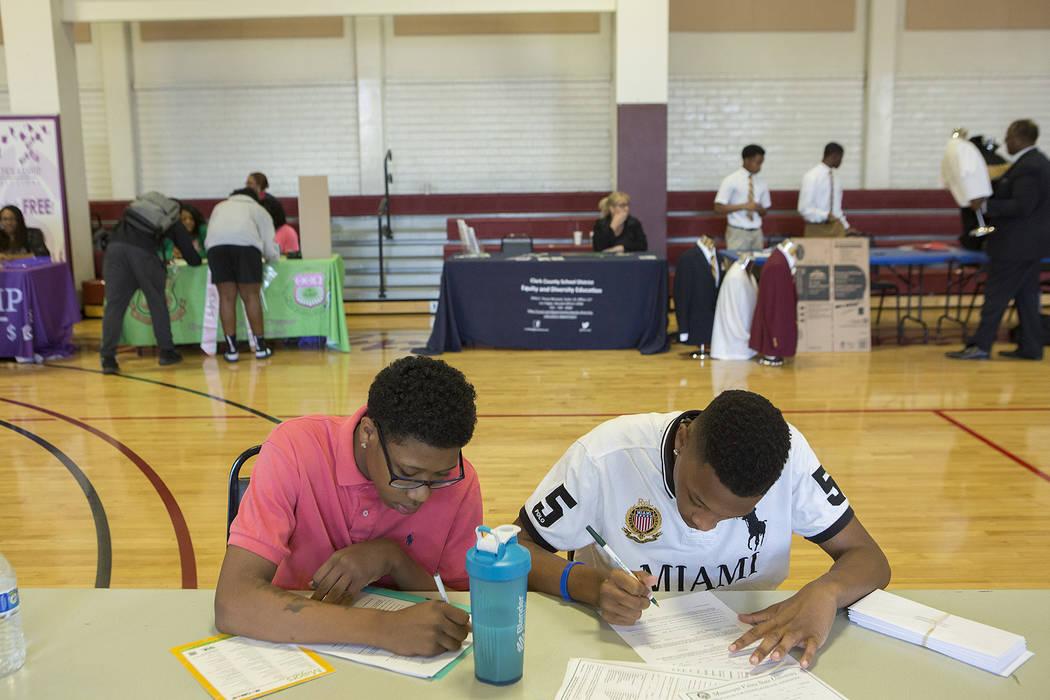 Shadow Ridge senior Gerran Simon, left, and Legacy senior Emon Davis fill out paperwork during the 18th annual Historically Black Colleges & Universities Recruitment Fair at  Doolittle Communi ...