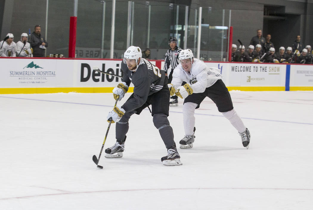 Vegas Golden Knights left defenseman Shea Theodore, left, (27) breaks away from Golden Knights defenseman Dmitry Osipov (79) in a scrimmage game during the NHL team's practice at the City National ...