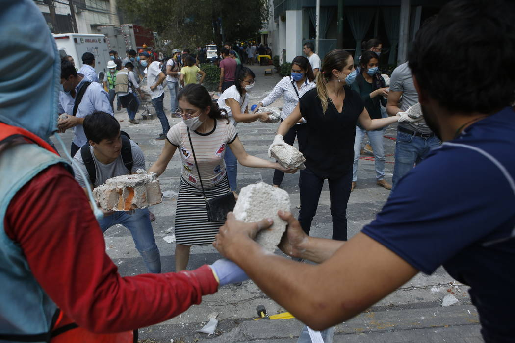 Volunteers pick up the rubble from a building that collapsed during an earthquake in the Condesa neighborhood of Mexico City, Tuesday, Sept. 19, 2017. A powerful earthquake jolted central Mexico o ...