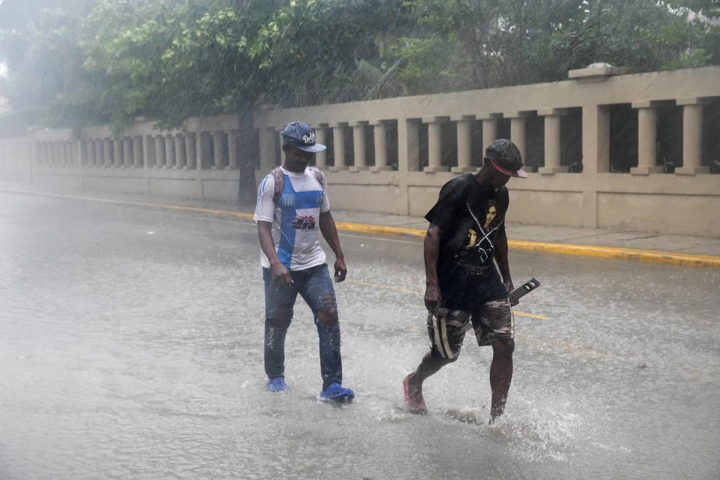 Men wade through a flooded Alemania Avenue as Hurricane Maria reaches the coast of Bavaro, Dominican Republic, Wednesday, Sept. 20, 2017. (Tatiana Fernandez/AP)