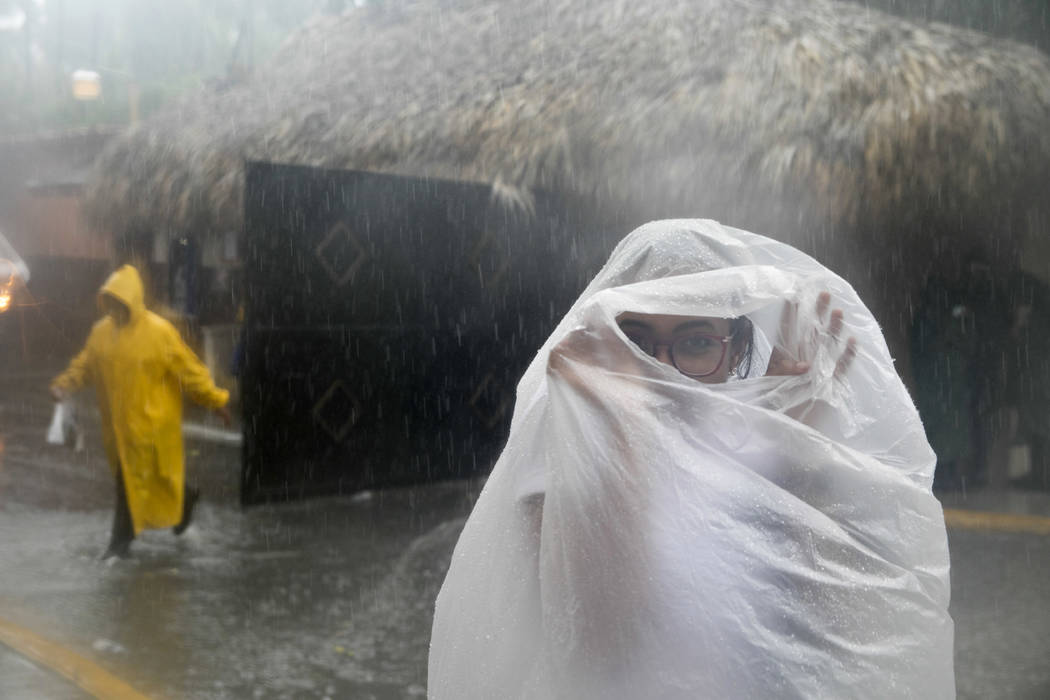 A woman covers herself with a plastic bag as she makes her way to work as Hurricane Maria approaches the coast of Bavaro, Dominican Republic, Wednesday, Sept. 20, 2017. (Tatiana Fernandez/AP)