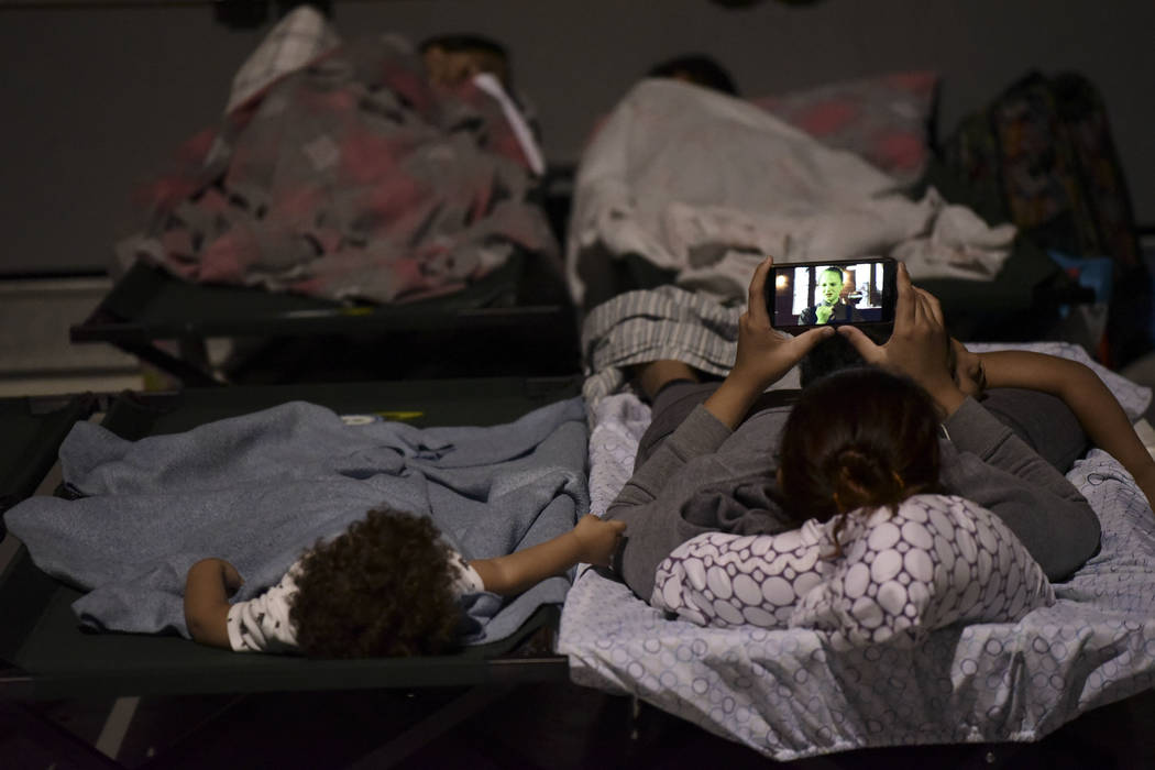 A woman and a child rest on cots while waiting at Humacao Arena refugee center for the imminent impact of Maria, a Category 5 hurricane that threatens to hit the eastern region of the island with  ...