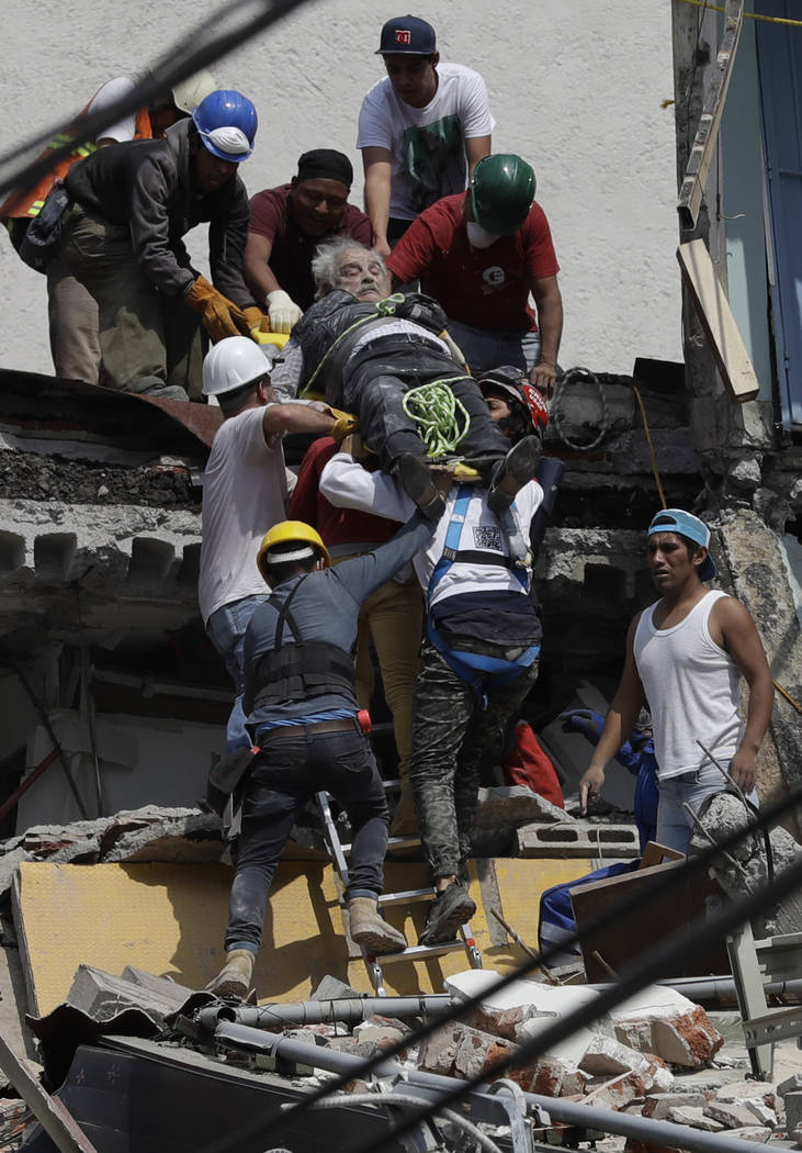 An injured man is pulled out of a building that collapsed during an earthquake in the Roma Norte neighborhood of Mexico City, Tuesday, Sept. 19, 2017. A powerful earthquake jolted central Mexico o ...