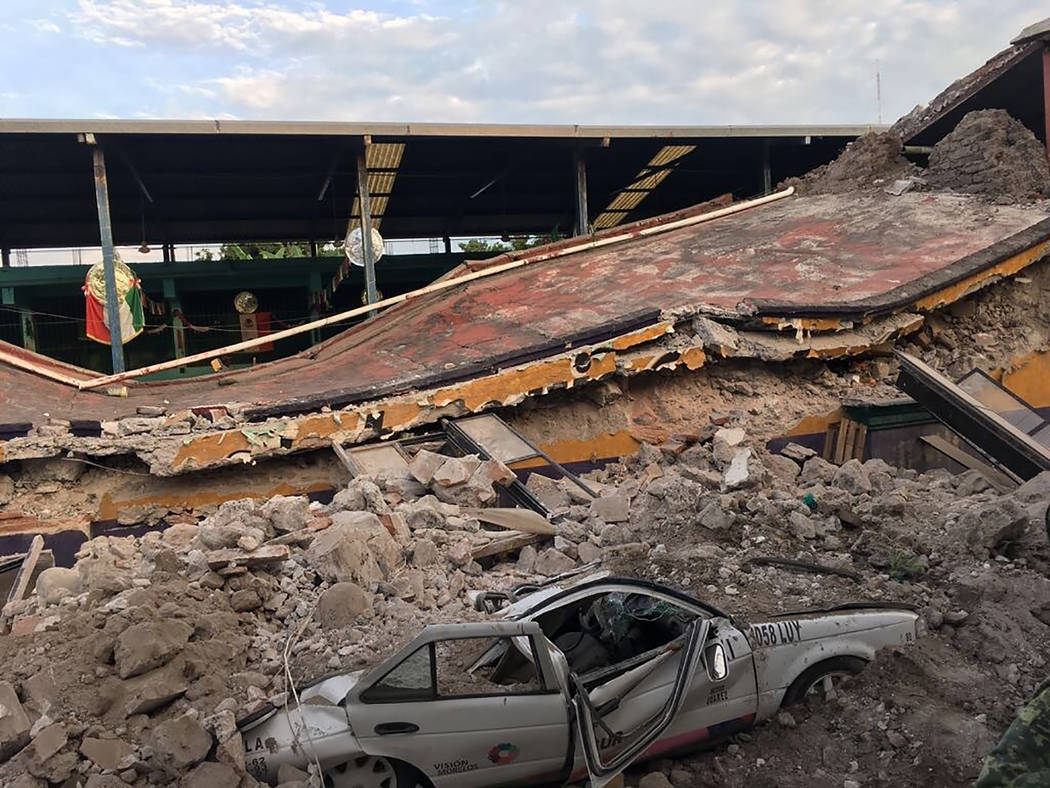 A car sits crushed, engulfed in a pile of rubble from a building felled by a 7.1 earthquake, in Jojutla, Morelos state, Mexico, Tuesday, Sept. 19, 2017. The earthquake stunned central Mexico, kill ...