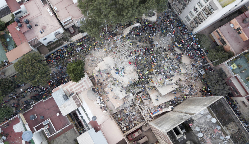 Rescue workers and volunteers search for survivors on a collapsed building the Del Valle neighborhood in Mexico City, Tuesday Sept. 19, 2017. A magnitude 7.1 earthquake has stunned central Mexico, ...