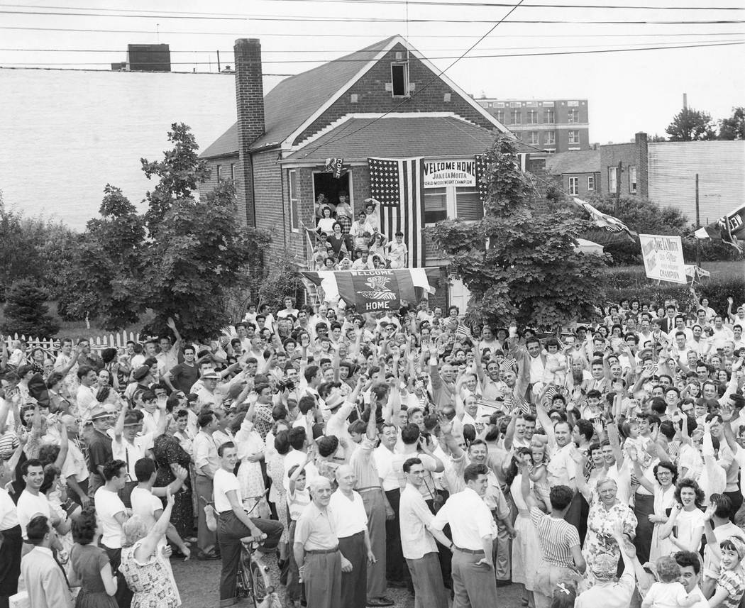 A crowd gathers in front of Jake Lamotta's home in the Bronx borough of New York, welcoming him home, June 18, 1949, from Detroit where he won the middleweight boxing championship against Marcel C ...