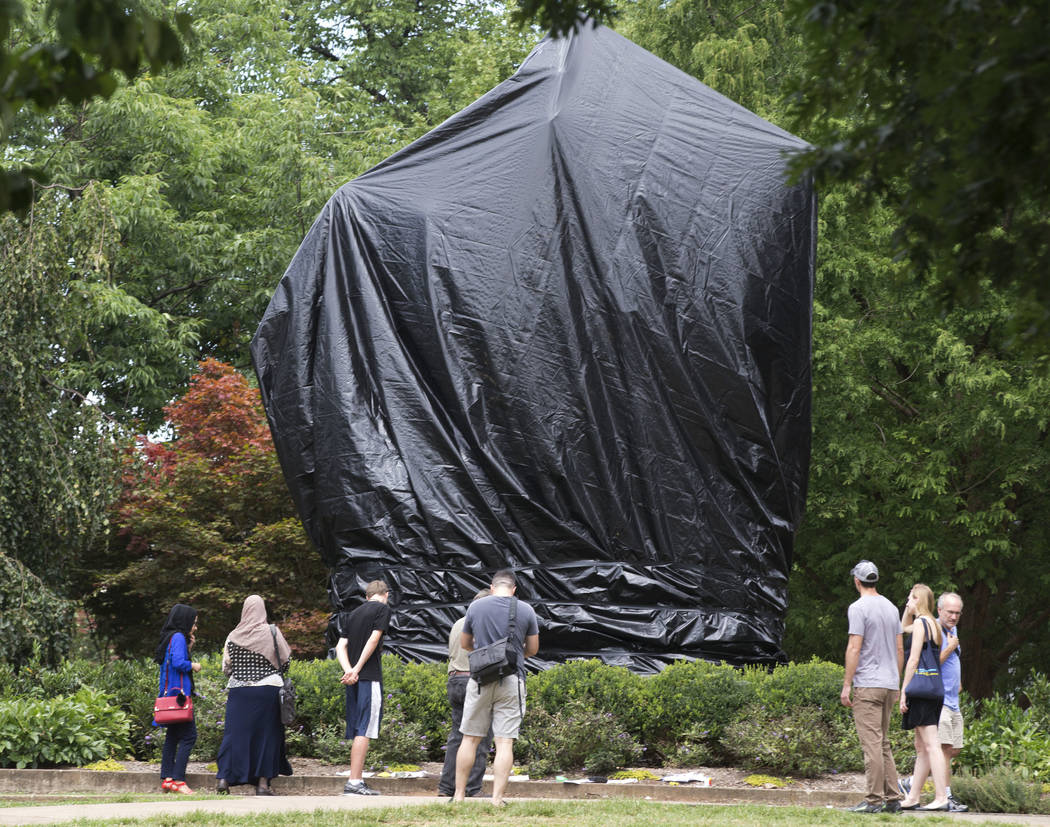 FILE - In this Wednesday, Aug. 23, 2017 file photo, people look at the covered statue of Confederate Gen. Robert E. Lee in Emancipation Park in Charlottesville, Va. The move to cover the statues w ...