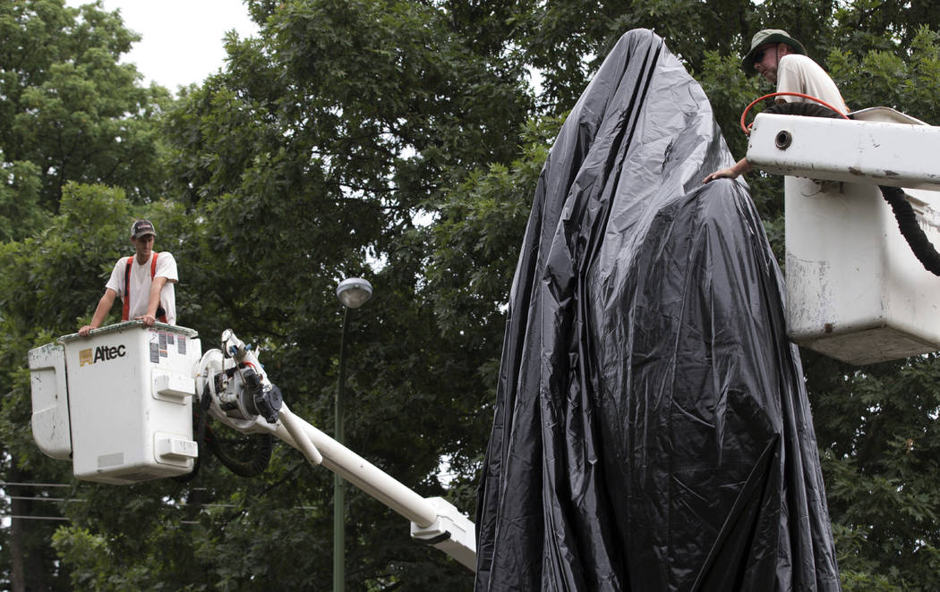 City workers drape a tarp over the statue of Confederate General Robert E. Lee in Emancipation park in Charlottesville, Va., Wednesday, Aug. 23, 2017. The move intended to symbolize the city's mou ...