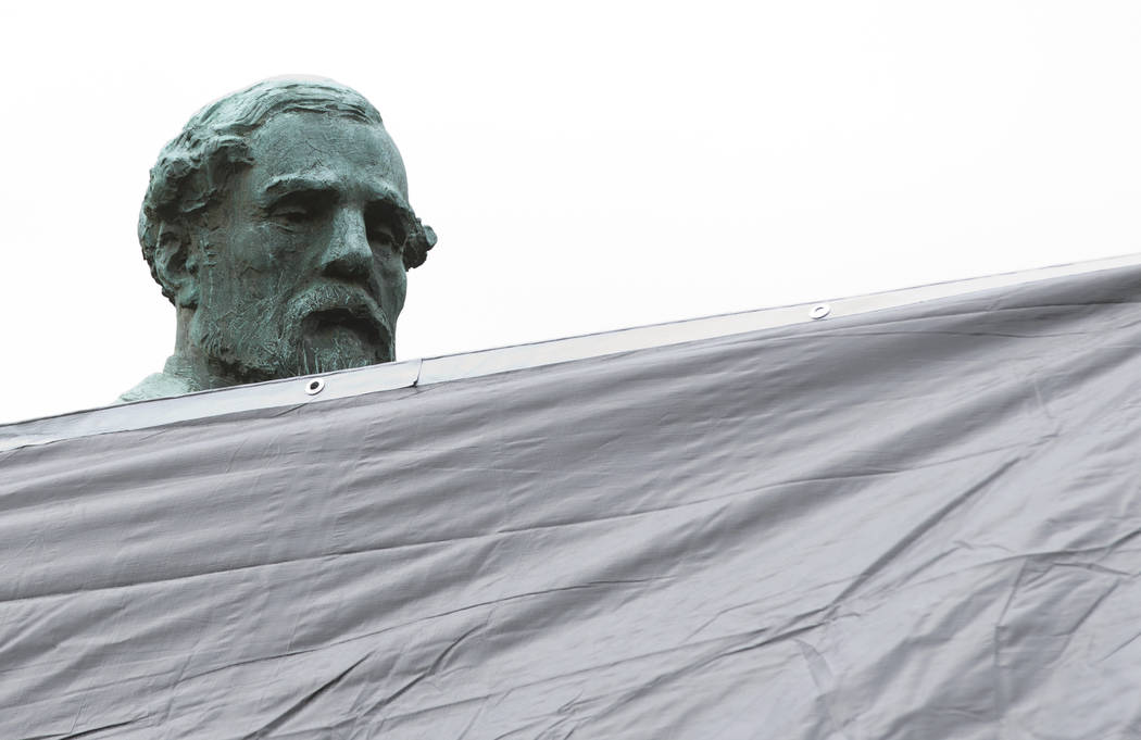 City workers drape a tarp over the statue of Confederate General Robert E. Lee in Emancipation park in Charlottesville, Va., Wednesday, Aug. 23, 2017. The move to cover the statues is intended to  ...