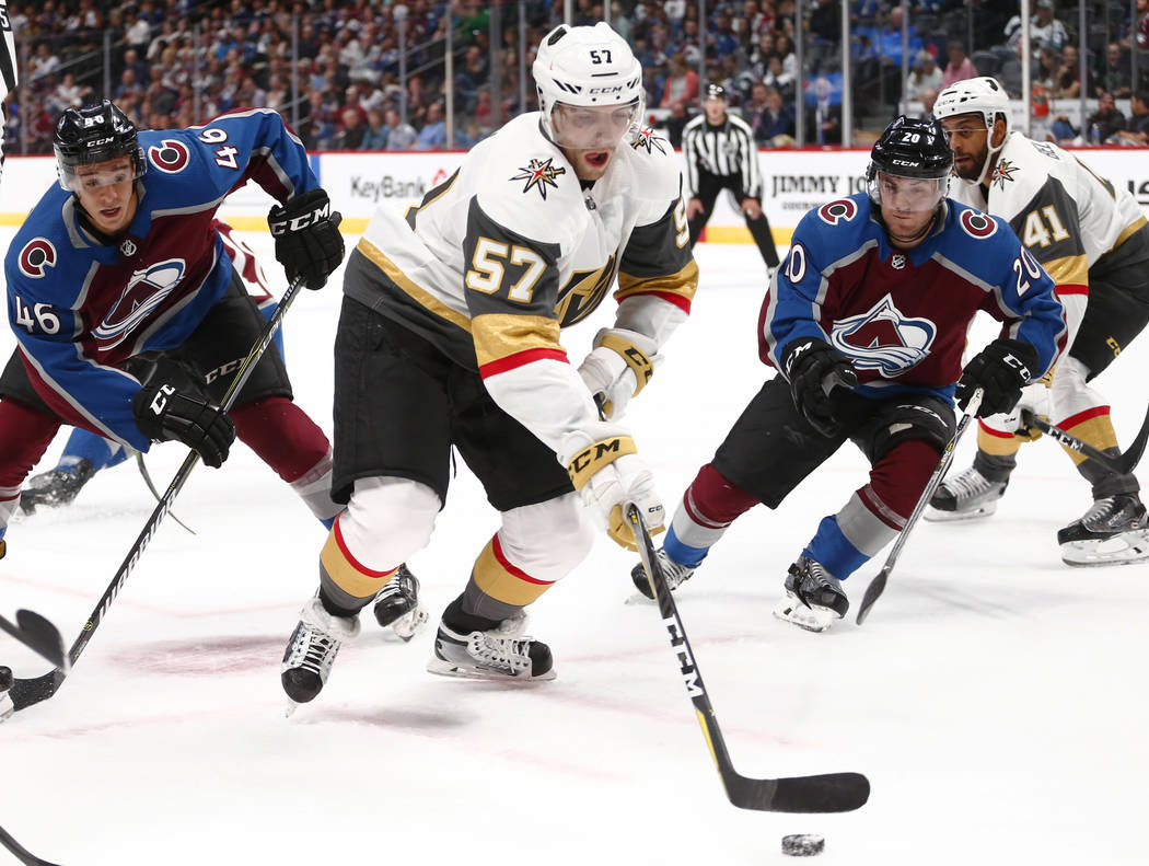 Las Vegas Golden Knights left wing David Perron (57) moves the puck away from Colorado Avalanche center J.C Beaudin (46) and Rocco Grimaldi (20) during the first period of a preseason hockey game, ...