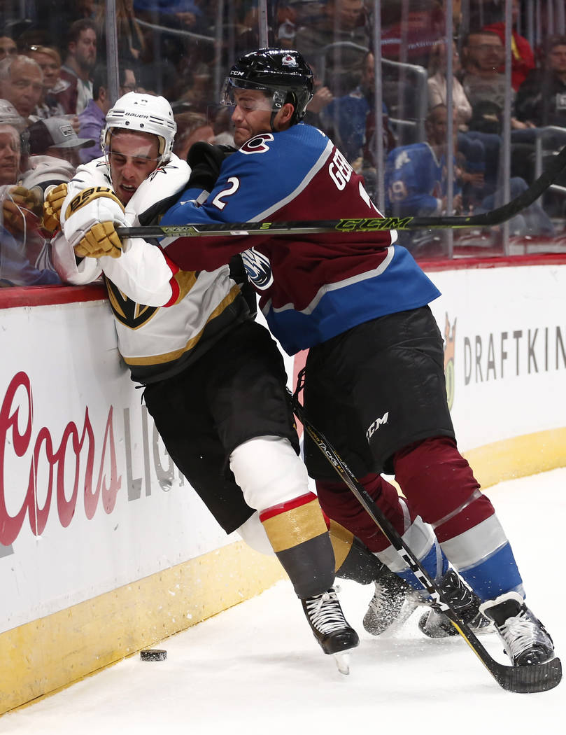 Las Vegas Golden Knights right wing Reilly Smith (19) is checked into the boards by Colorado Avalanche defenseman Mason Geertsen (2) during the second period of a preseason hockey game, Tuesday, S ...