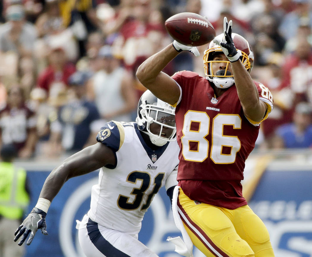 Washington Redskins tight end Jordan Reed, right, catches as Los Angeles Rams strong safety Maurice Alexander looks on during the first half of an NFL football game Sunday, Sept. 17, 2017, in Los  ...