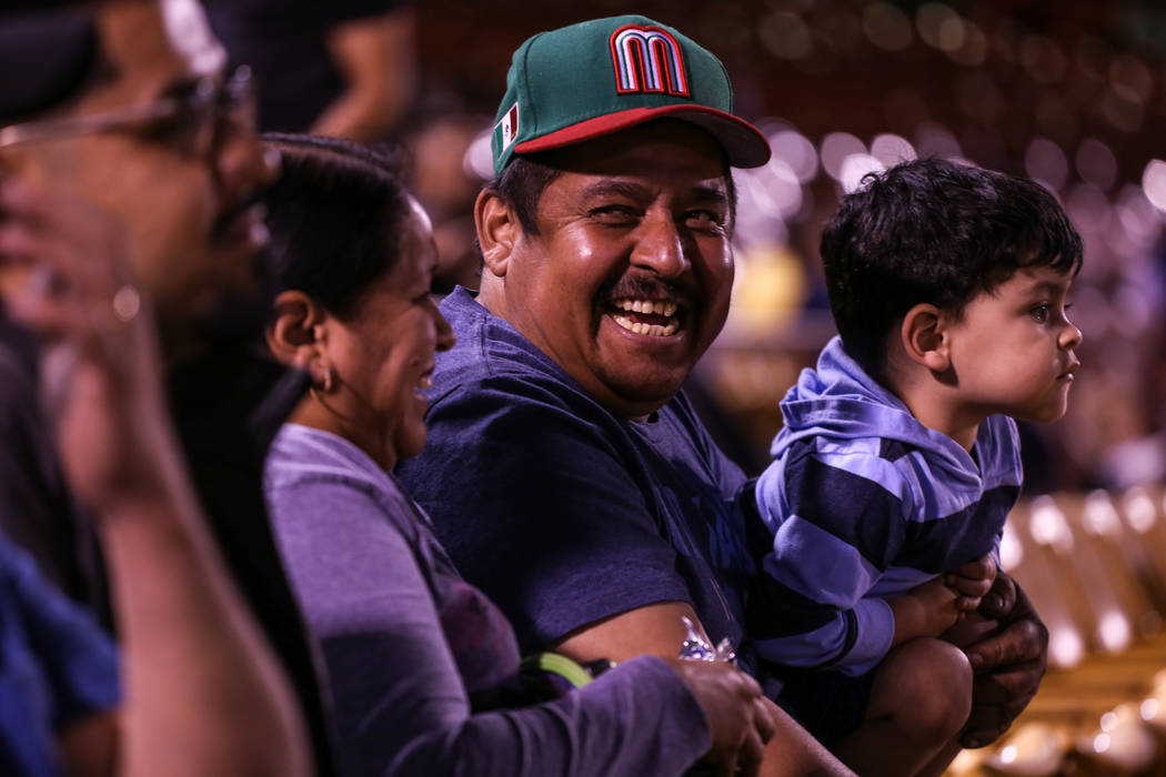 Jesus Cuevas, left, laughs as he holds his nephew Jesus Alexander Cuevas, 2, on his lap during a baseball game between the Naranjeros de Hermosillo and Aguilas de Mexicali at the Cashman Field in  ...