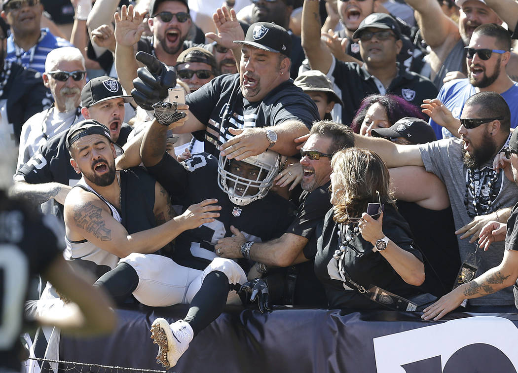 Oakland Raiders running back Jalen Richard, center, celebrates with fans after scoring a touchdown against the New York Jets during the second half of an NFL football game in Oakland, Calif., Sund ...