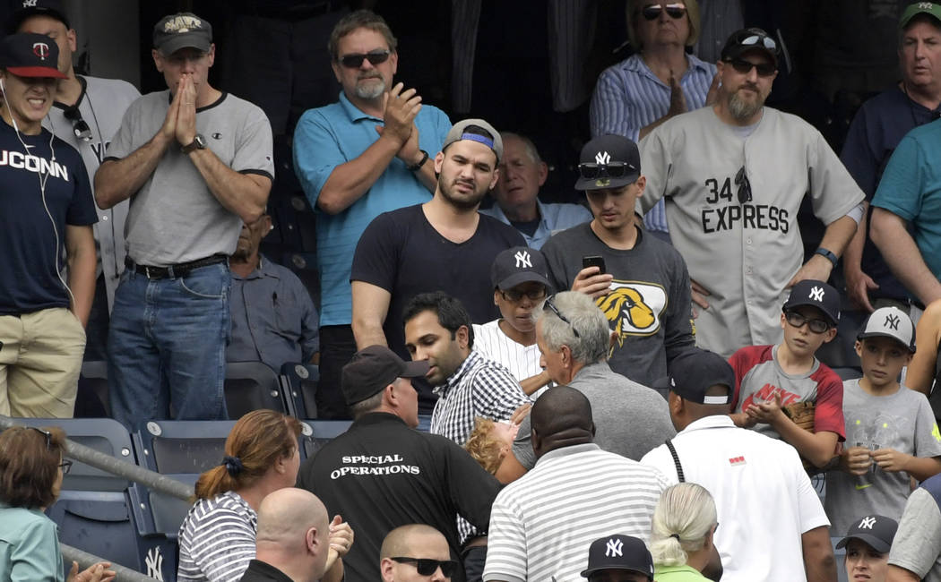 Baseball fans reacts as a young girl is carried out of the seating area after being hit by a line drive during the fifth inning of a baseball game between the New York Yankees and Minnesota Twins, ...