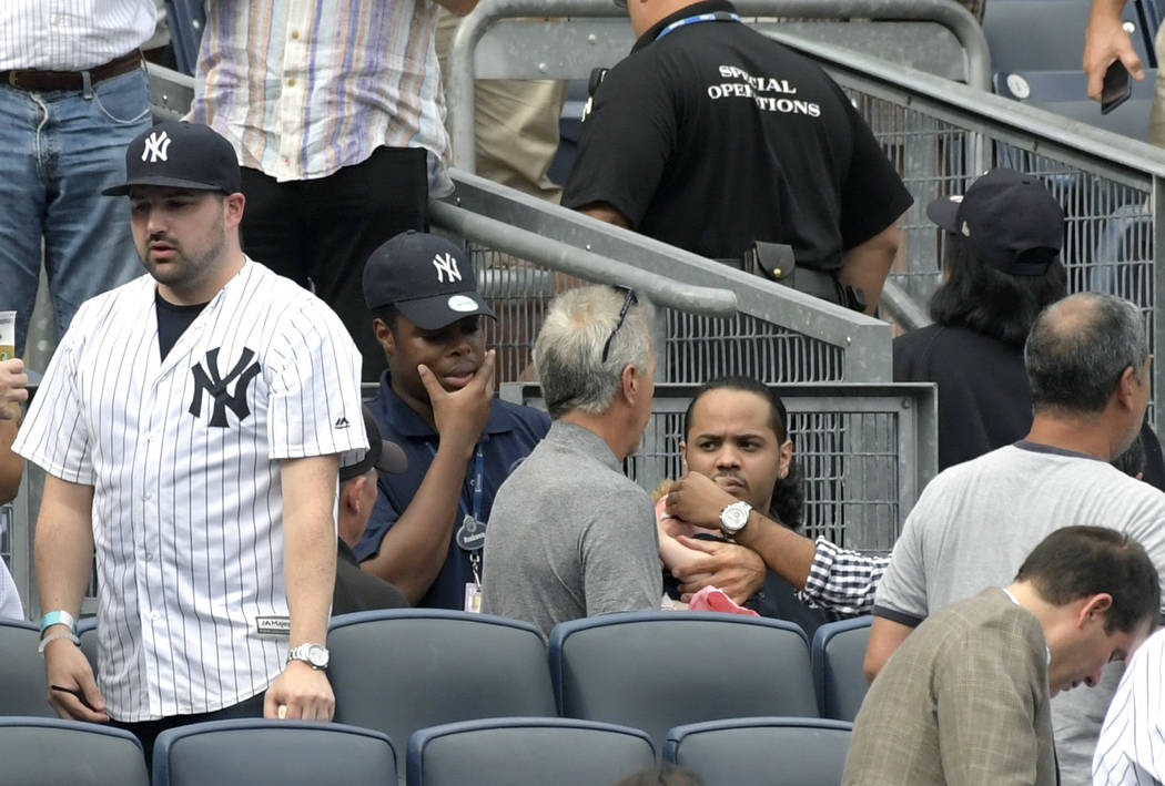 Baseball fans reacts as a young girl is tended to before she is carried out of the seating area after being hit by a line drive in the fifth inning of a baseball game between the New York Yankees  ...