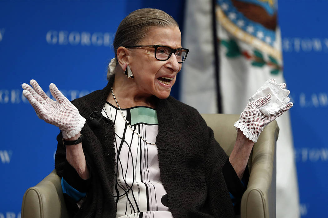 U.S. Supreme Court Justice Ruth Bader Ginsburg reacts to applause as she is introduced by William Treanor, Dean and Executive Vice President of Georgetown University Law Center, at the Georgetown  ...