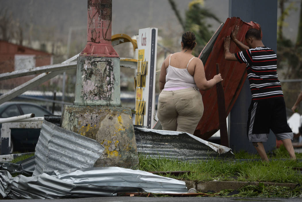 Residents move aluminum panels from an intersection after Hurricane Maria hit the eastern region of the island, in Humacao, Puerto Rico, Wednesday, Sept. 20, 2017. The strongest hurricane to hit P ...