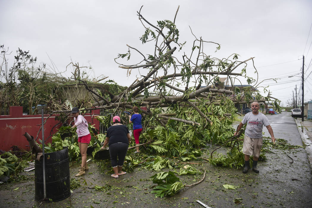 A family helps clean the road after Hurricane Maria hit the eastern region of the island, in Humacao, Puerto Rico, Tuesday, September 20, 2017. The strongest hurricane to hit Puerto Rico in more t ...