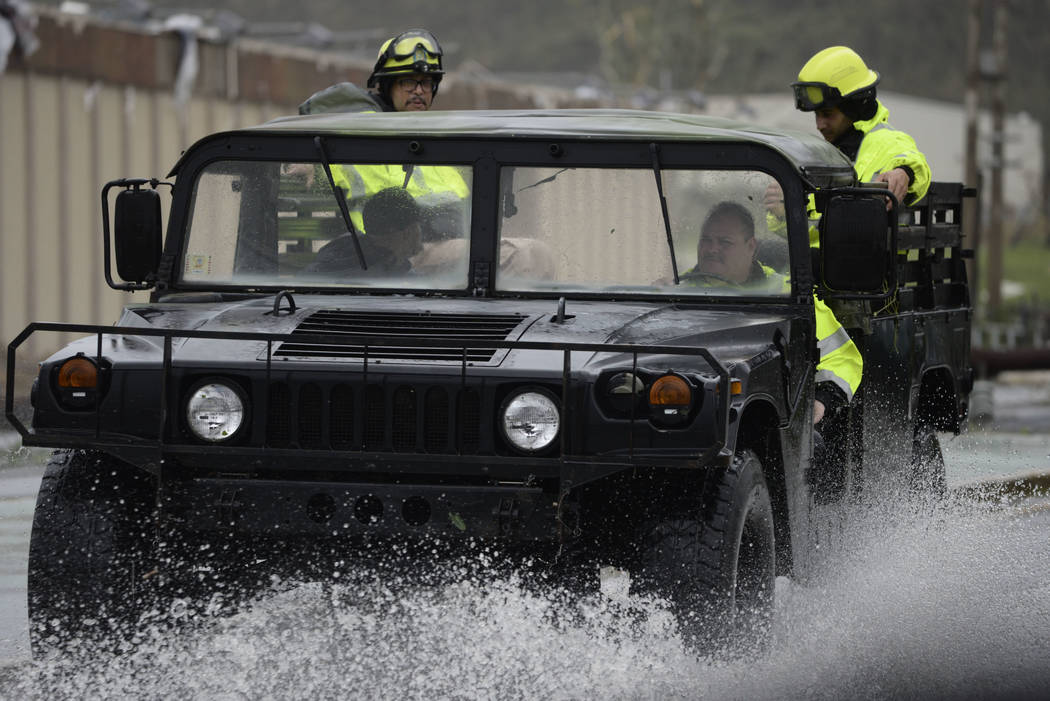 Rescue personnel from the Emergency Management Agency drive through a flooded road after Hurricane Maria hit the eastern region of the island, in Humacao, Puerto Rico, Tuesday, September 20, 2017. ...