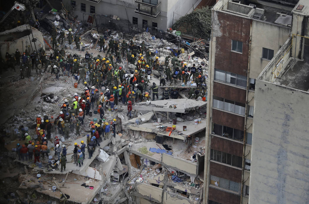 Rescue workers search for people trapped inside a collapsed building felled by a 7.1 magnitude earthquake in the Del Valle area of Mexico City, Wednesday, Sept. 20, 2017. Tuesday's magnitude-7.1 q ...