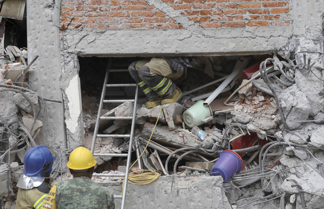 A rescue worker climbs up into an apartment building whose first four floors collapsed in the Lindavista neighborhood of Mexico City, Wednesday, Sept. 20, 2017. (Rebecca Blackwell/AP)
