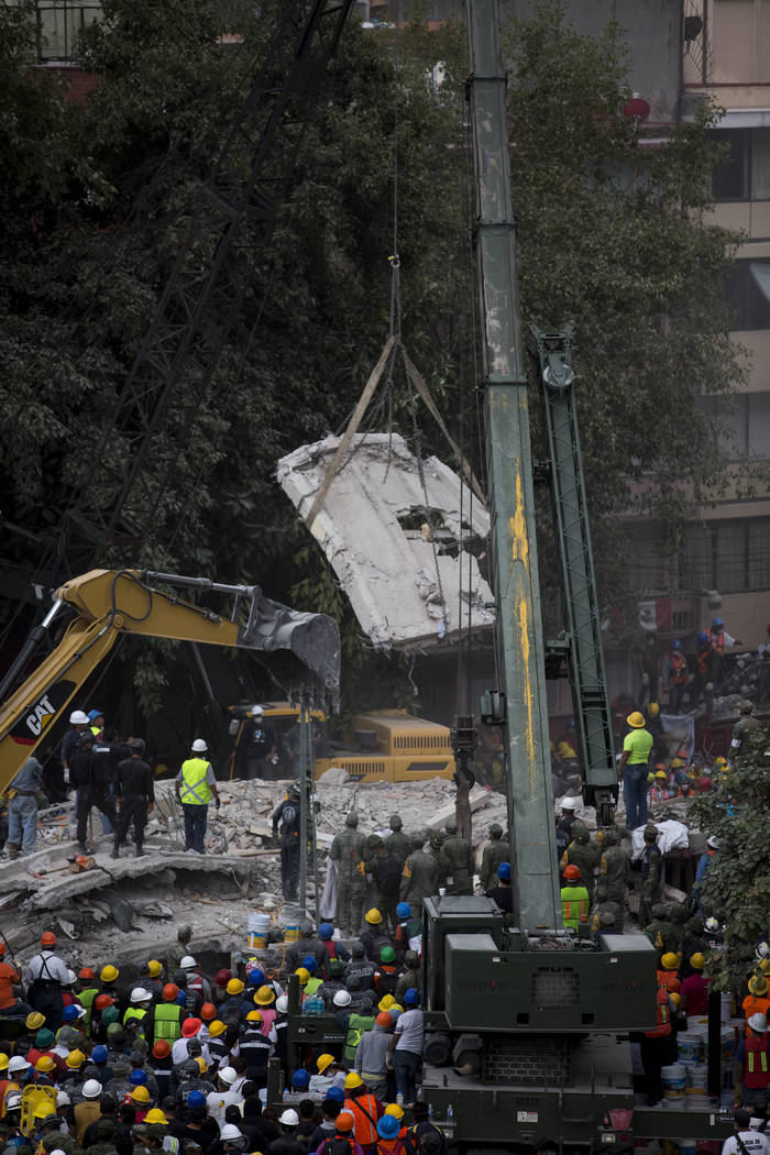 A crane moves a piece of a collapsed building, a day after a devastating 7.1 earthquake in the Del Valle neighborhood of Mexico City, Wednesday, Sept. 20, 2107. Efforts continue at the scenes of d ...