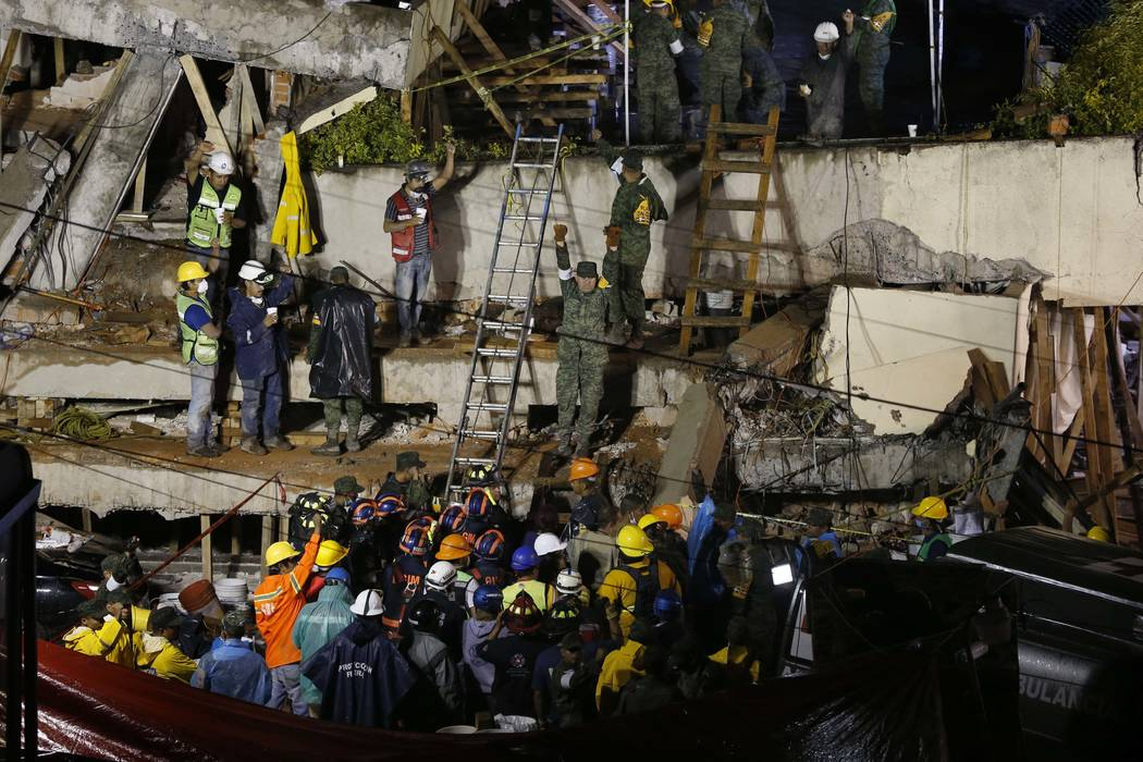 Rescue personnel work on the rescue of a trapped child at the collapsed Enrique Rebsamen primary school in Mexico City, Sept. 20, 2017. A wing of the school collapsed after a powerful earthquake j ...