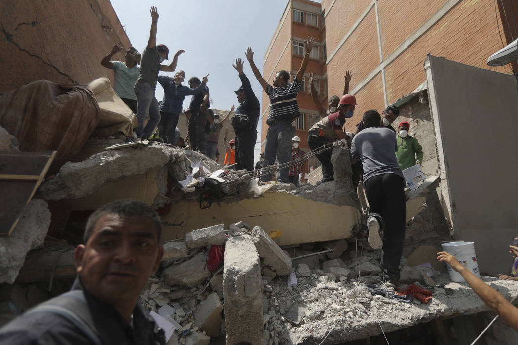 Rescue workers and volunteers search for survivors in the aftermath of a 7.1 magnitude earthquake, at the Ninos Heroes neighborhood in Mexico City, Tuesday, Sept. 19, 2017. Workers, some wearing h ...