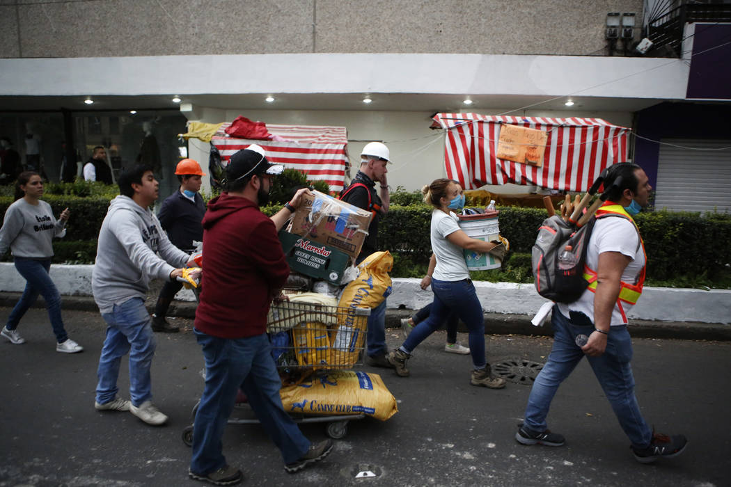 Volunteers offering their services at sites of earthquake damage mingle with people taking donations of pet food to a collection center as they walk along Insurgentes Avenue in the Roma neighborho ...