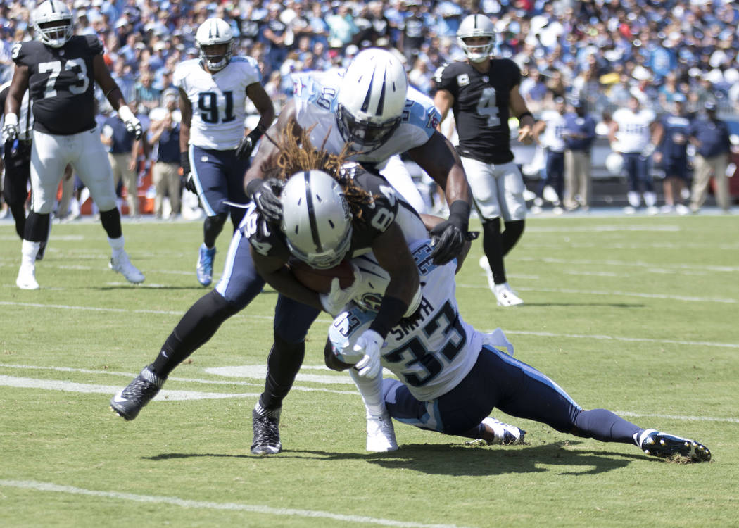 Oakland Raiders wide receiver Cordarrelle Patterson (84) is tackled by defenders in the first half of the NFL game against the Tennessee Titans at the Nissan Stadium in Nashville, Tenn., Sunday, S ...