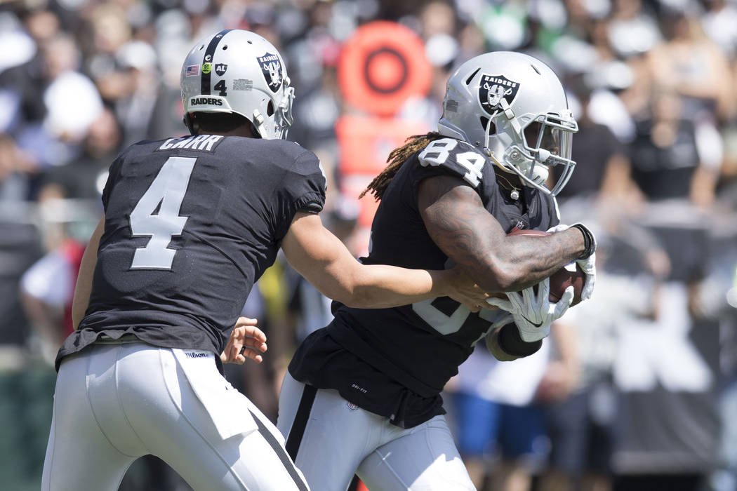 Oakland Raiders quarterback Derek Carr (4) hands off to wide receiver Cordarrelle Patterson (84) in the first half of the game against the New York Jets in Oakland, Calif., Sunday, Sept. 17, 2017. ...