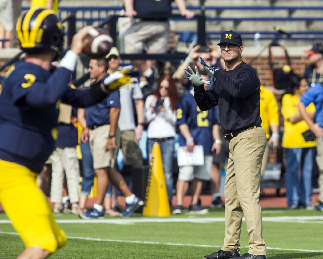 Michigan quarterback Wilton Speight (3) throws a pass to head coach Jim Harbaugh during warmups before an NCAA college football game against Air Force in Ann Arbor, Mich., Saturday, Sept. 16, 2017 ...