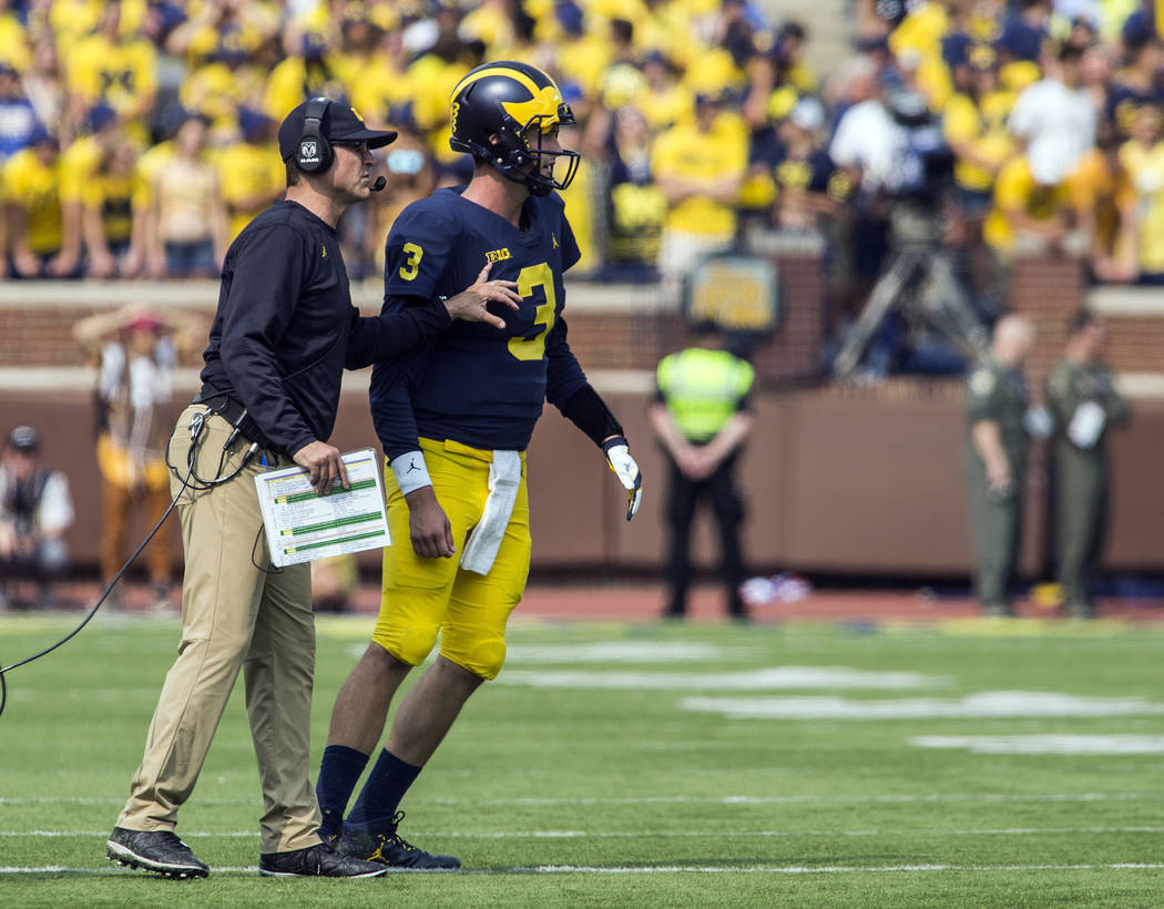Michigan head coach Jim Harbaugh, left, gives instructions to Michigan quarterback Wilton Speight (3) in the fourth quarter of an NCAA college football game against Air Force in Ann Arbor, Mich.,  ...