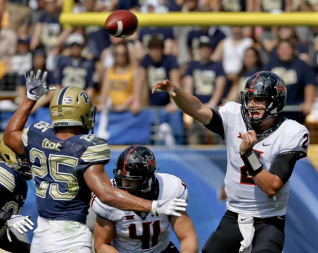 Oklahoma State quarterback Mason Rudolph (2) passes over Pittsburgh linebacker Elijah Zeise (25) in the first quarter of an NCAA football game, Saturday, Sept. 16, 2017, in Pittsburgh. Oklahoma St ...
