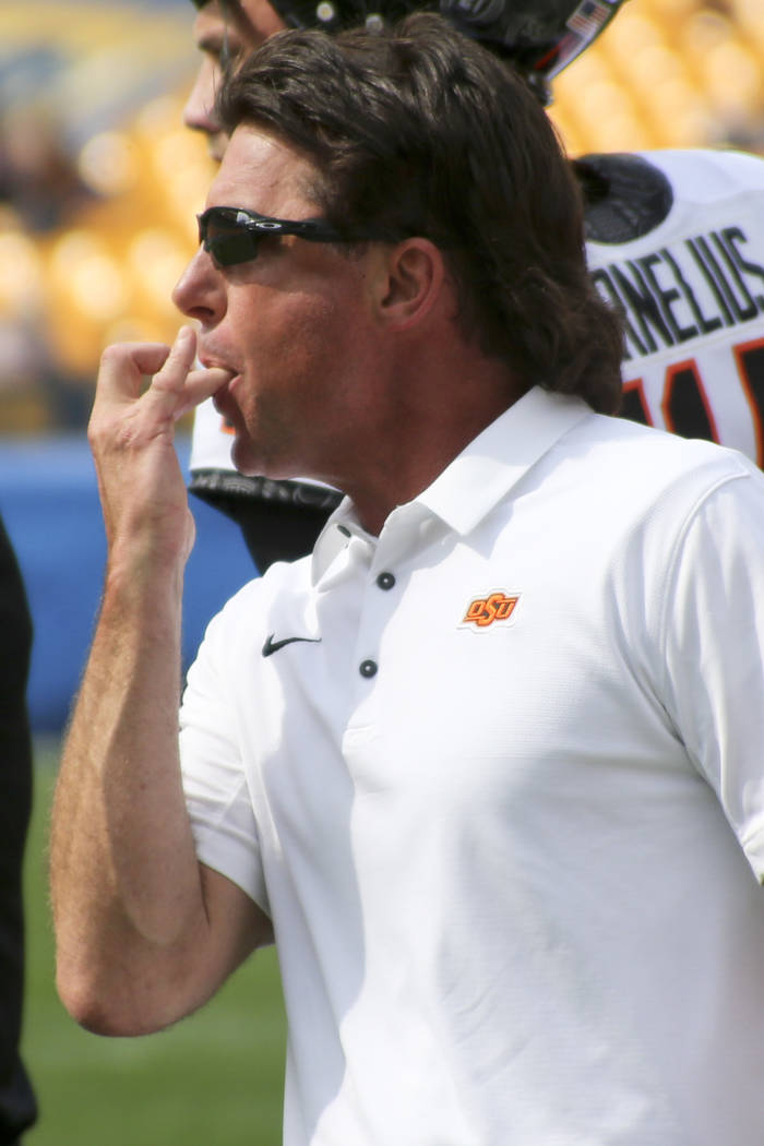 Oklahoma State head coach Mike Gundy whistles to get the attention of the officials in the fourth quarter of an NCAA football game Pittsburgh, Saturday, Sept. 16, 2017, in Pittsburgh. Oklahoma Sta ...