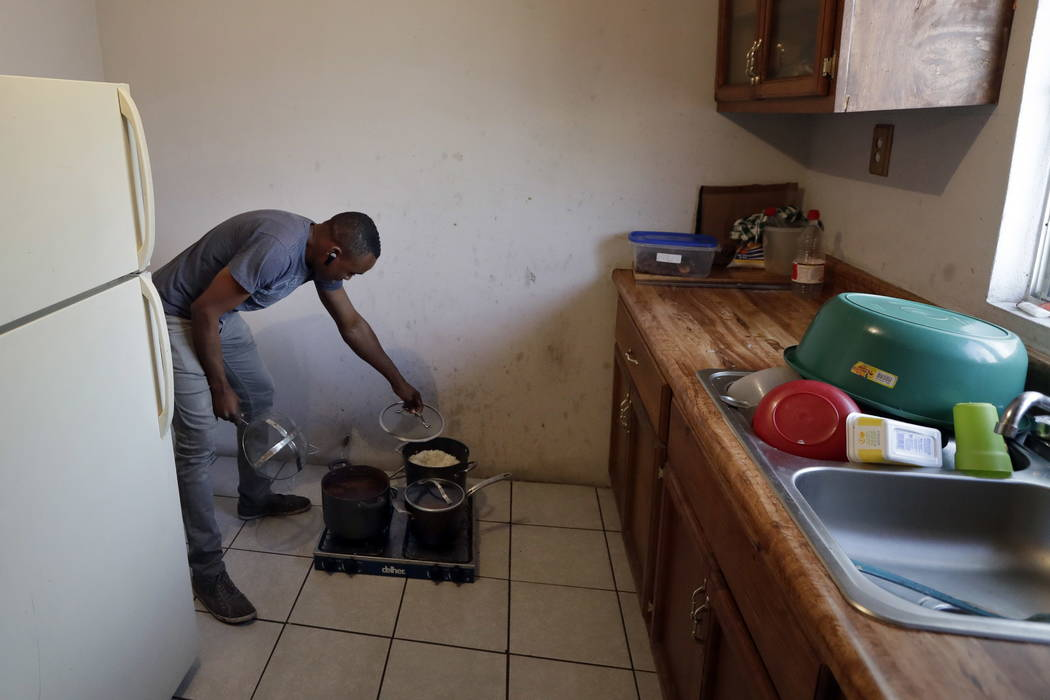 Abelson Etienne removes the top to a pot of rice on a stove in his apartment in Tijuana, Mexico, on June 6. (AP Photo/Gregory Bull)