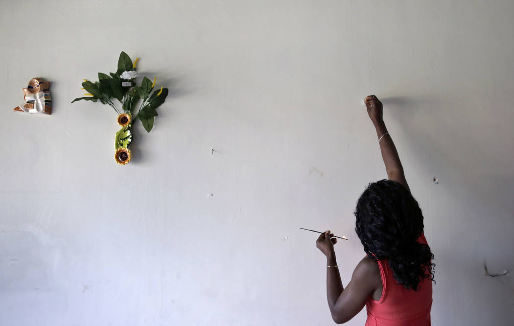 Lucy Charles, of Haiti, lights incense along a wall in her restaurant specializing in Haitian cuisine in Tijuana, Mexico, on May 24. (AP Photo/Gregory Bull)