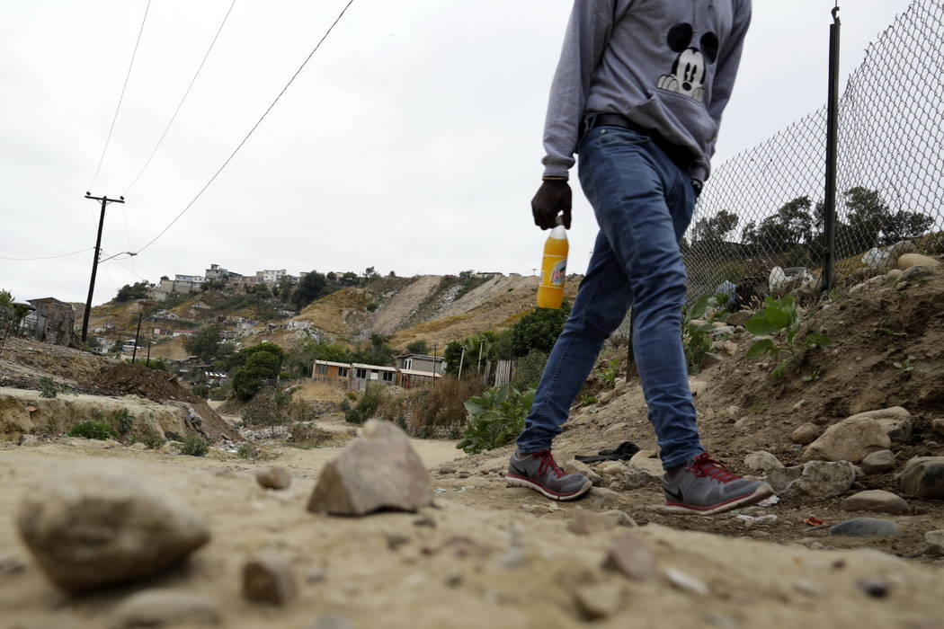 A Haitian man makes his way up a dirt road towards a makeshift shelter at The Ambassadors of Jesus Church in Tijuana, Mexico, on May 24.  (AP Photo/Gregory Bull)